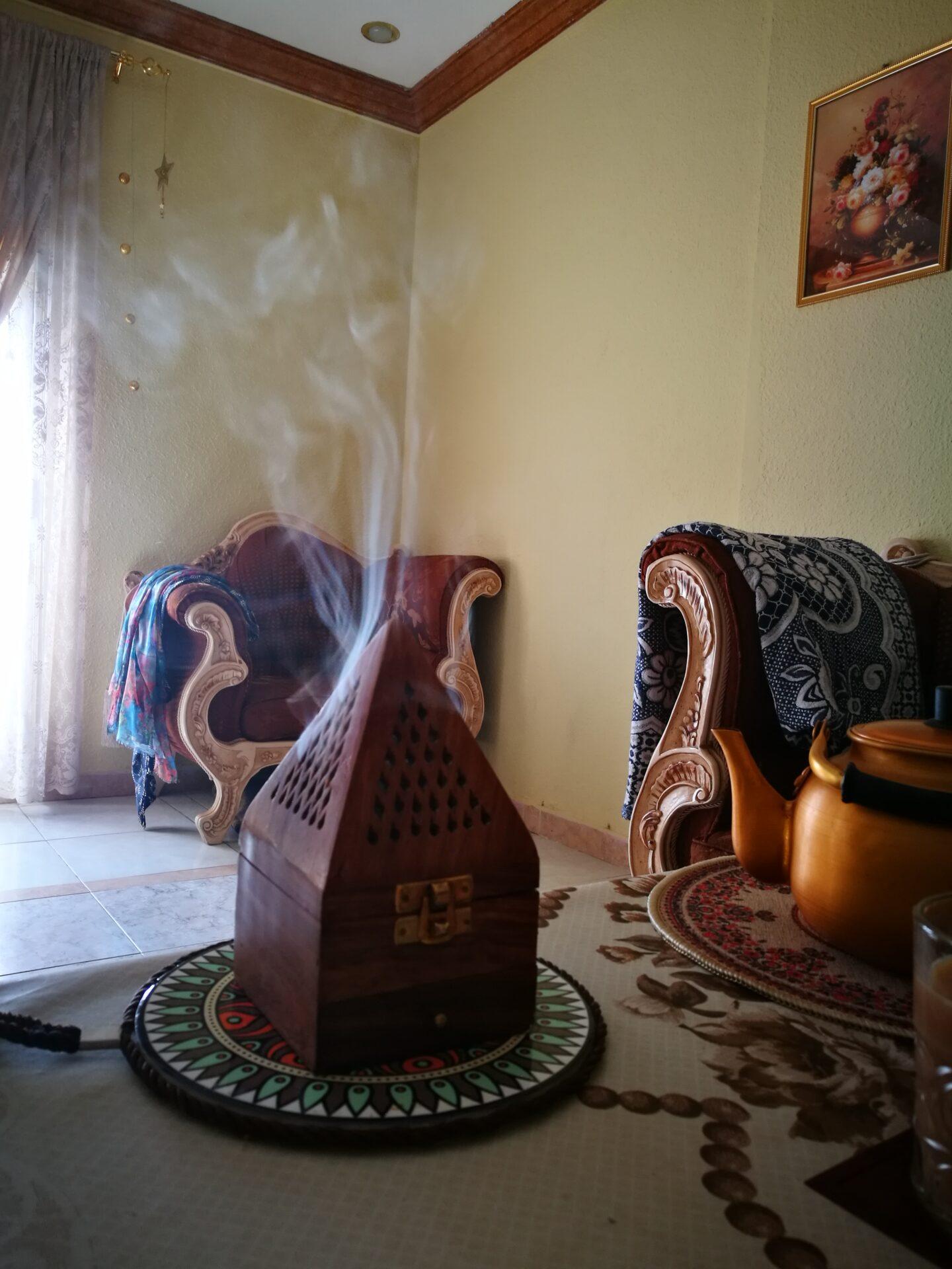 lesen podstavek/gorilnik za kadilo, iz njega prihaja dim; poleg je na mizici čajnik, v ozadju orientalsko pohištvo, skozi okno prihaja medla svetloba