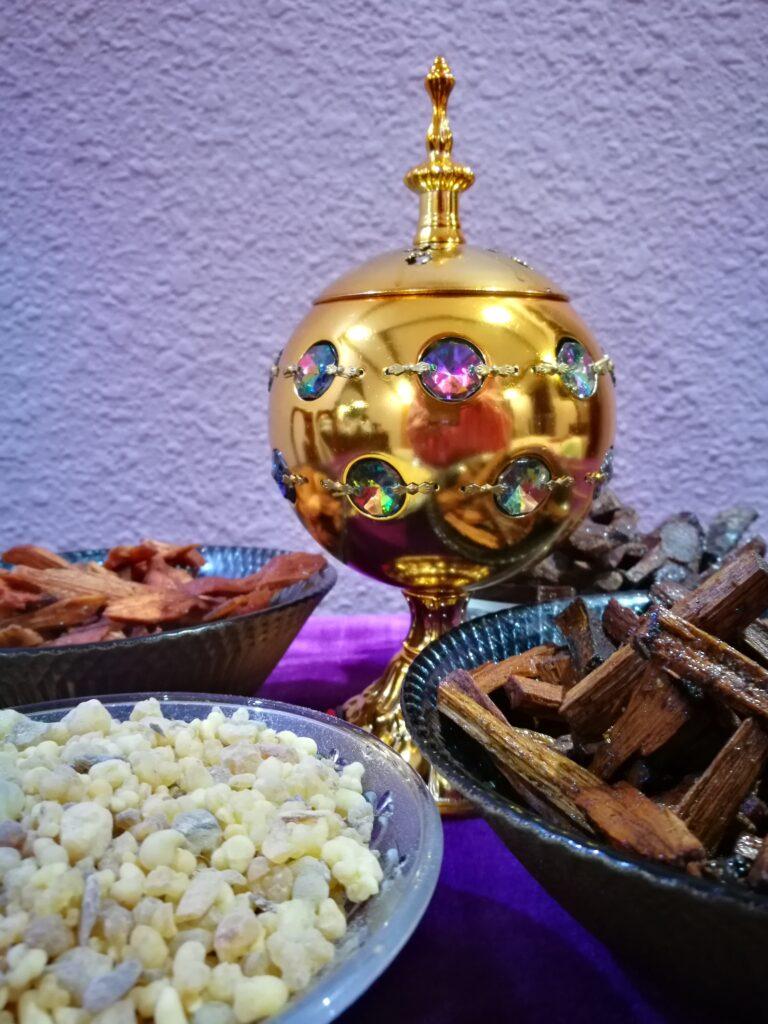 golden plated bakhoor burner, different kind of incense around it in bowls