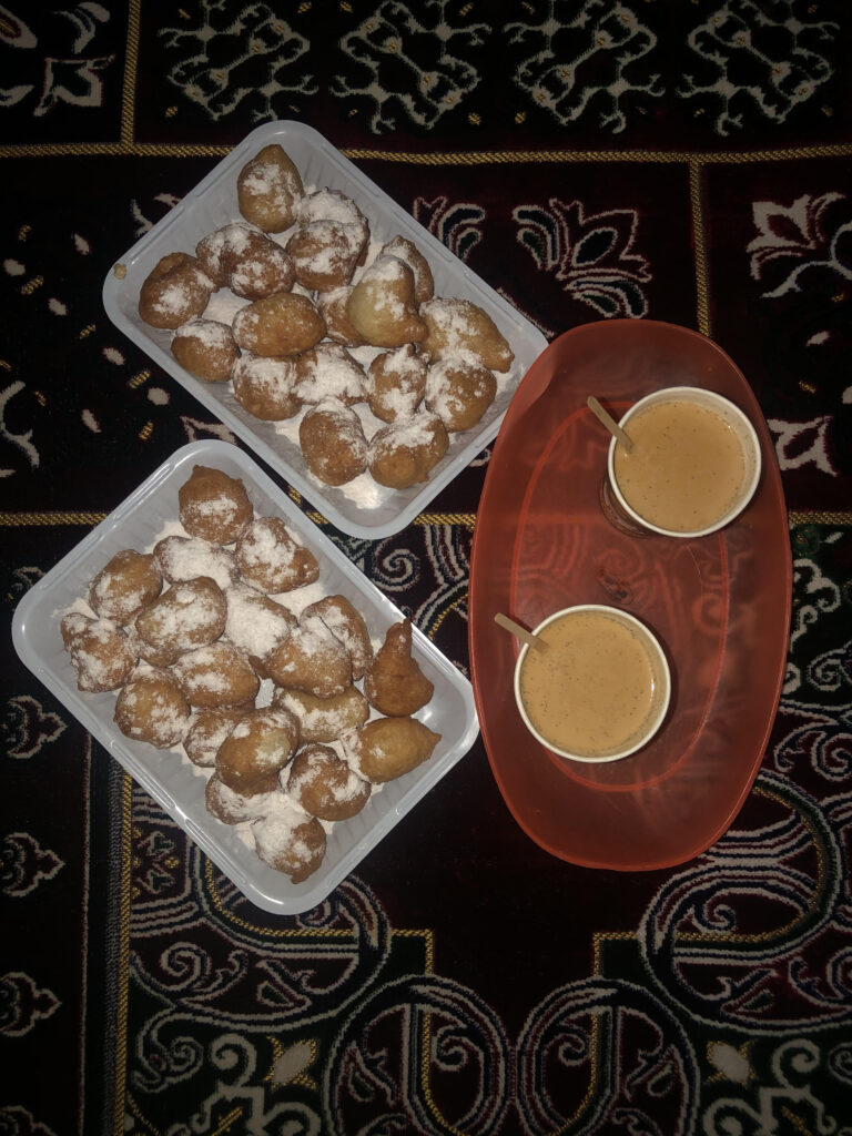 Sudanese zalabya and milk tea served on a carpet in a park